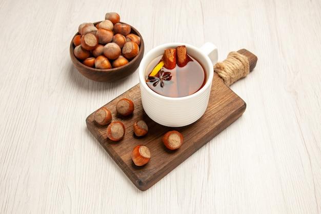 Tasse tee mit frischen haselnüssen auf weiß