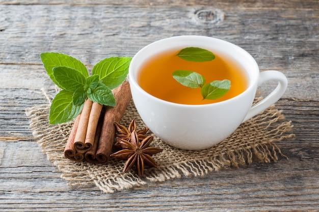 Tasse tee mit frischen tadellosen blättern und zimtanis auf holz