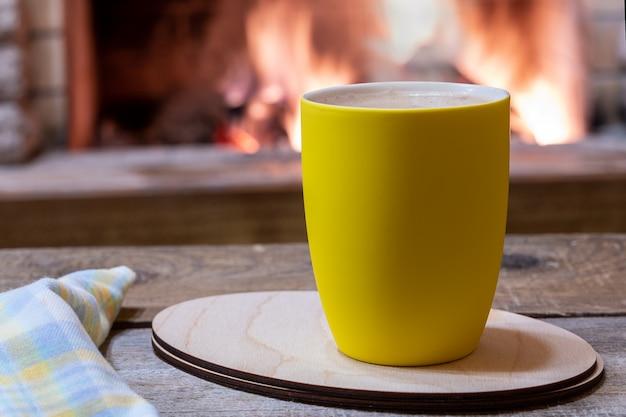 Tasse tee mit gemütlichem kamin im landhaus