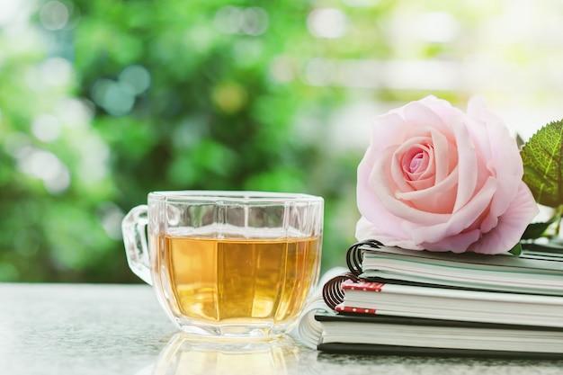 Tasse tee mit gewundenen notizbüchern und rosafarbener blume des süßen rosas