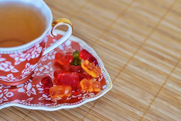 Tasse tee mit gummibärchen auf einer untertasse
