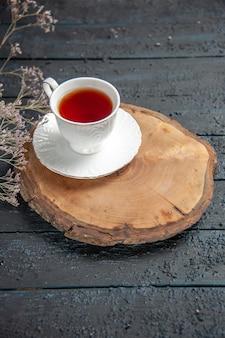 Tasse tee mit halber draufsicht auf dunklem tisch
