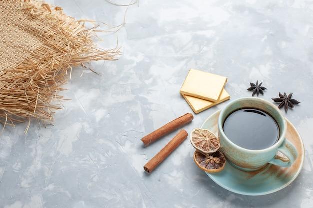 Tasse tee mit halber draufsicht mit bonbons und zimt auf weißem schreibtisch tee bonbon farbe frühstück