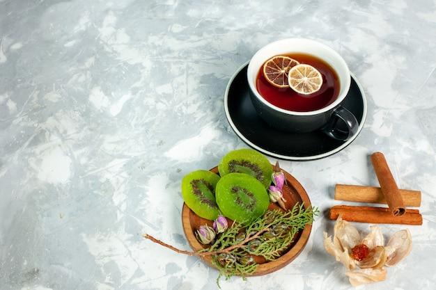 Tasse tee mit halber draufsicht mit kiwischeiben und zimt auf weißer oberfläche tee trinken blume zitrone