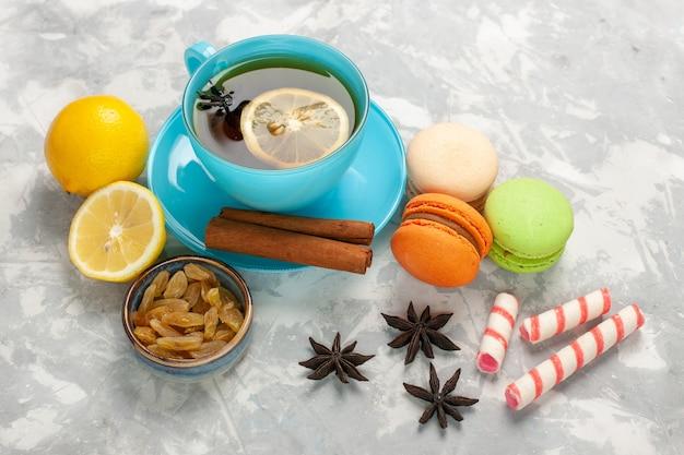 Tasse tee mit halber draufsicht mit macarons und rosinen auf der weißen oberfläche