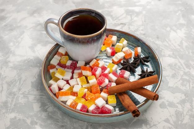 Tasse tee mit halber draufsicht mit marmelade und zimt auf hellweißer oberfläche