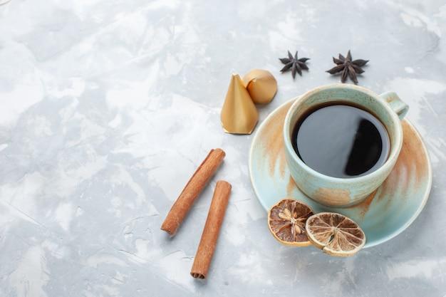 Tasse tee mit halber draufsicht und zimt auf dem weißen schreibtisch-tee-bonbon-farbfrühstück
