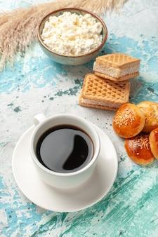 Tasse tee mit halber draufsicht, waffeln und kleinen kuchen auf blauer oberfläche