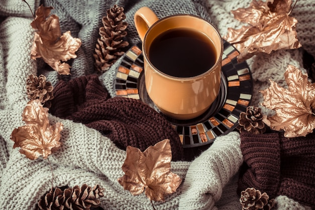 Tasse tee mit herbstlaub und pullover