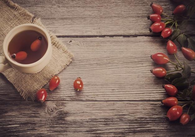 Tasse tee mit hippen rosen, auf holztisch