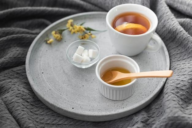 Tasse tee mit honig- und zuckerwürfeln