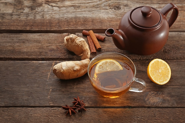 Tasse tee mit ingwer und zimt auf holzoberfläche