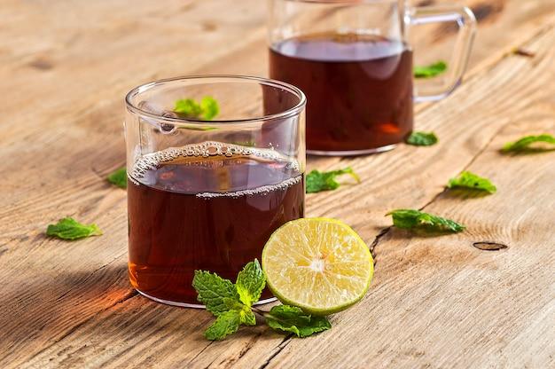 Tasse tee mit ingwer, zitrone und minze auf holztisch