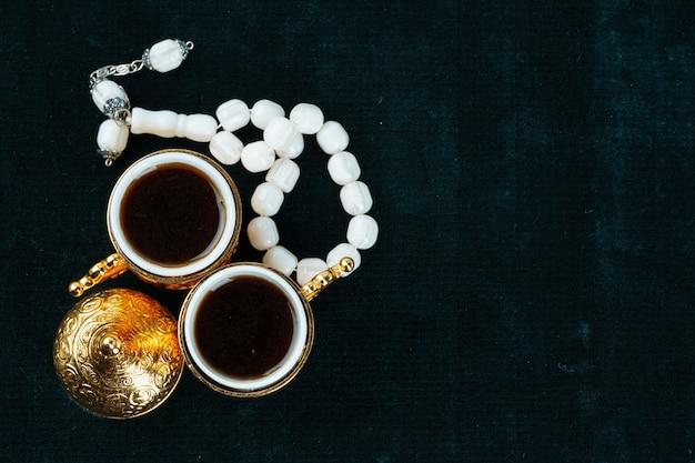 Tasse tee mit islamischen gebetsperlen