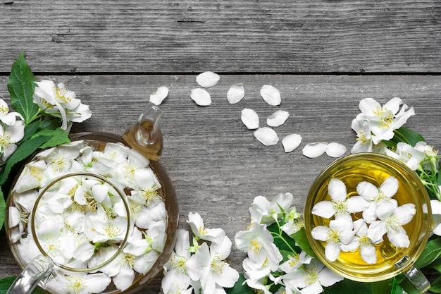 Tasse tee mit jasminblüten und teekanne auf einem hölzernen hintergrund