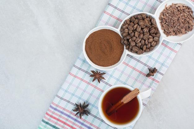 Tasse tee mit kaffeebohnen, gemahlenem kaffee und nelken auf tischdecke. foto in hoher qualität
