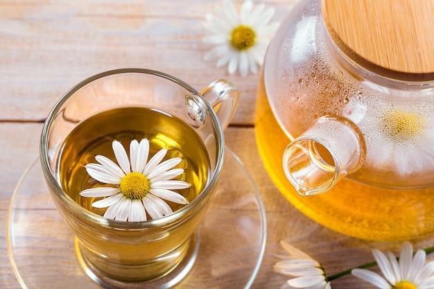 Tasse tee mit kamillenblumen auf hölzernem hintergrund
