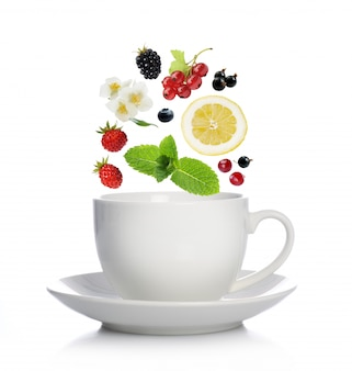 Tasse tee mit kräutern, früchten und beeren