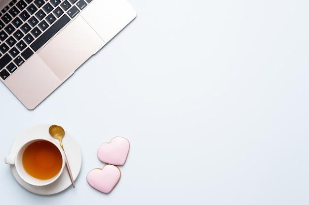 Tasse tee mit laptop und rosa herzen auf einem tisch