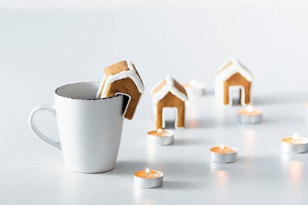 Tasse tee mit lebkuchenhaus neben kerzen. weihnachtsstimmung. gemütlichkeit.