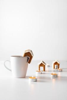 Tasse tee mit lebkuchenhaus und kerzen