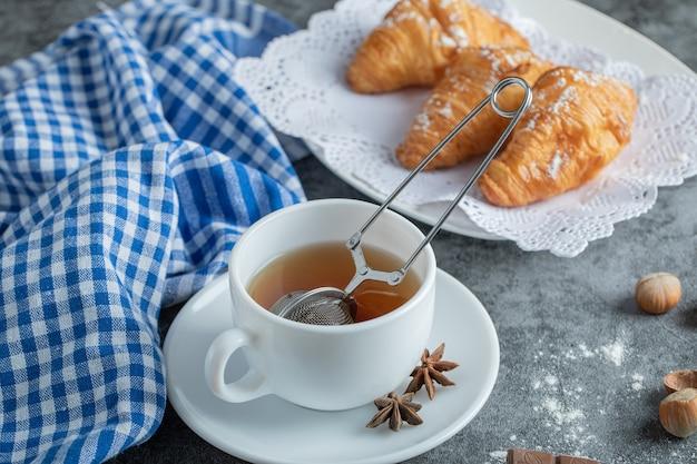 Tasse tee mit leckeren croissants auf marmoroberfläche.