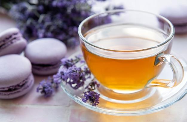 Tasse tee mit makronen-dessert mit lavendelgeschmack auf rosa fliesenhintergrund