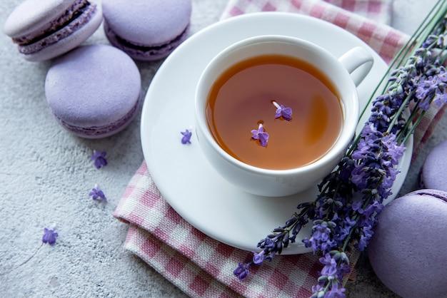 Tasse tee mit makronen-dessert mit lavendelgeschmack und frischen lavendelblüten