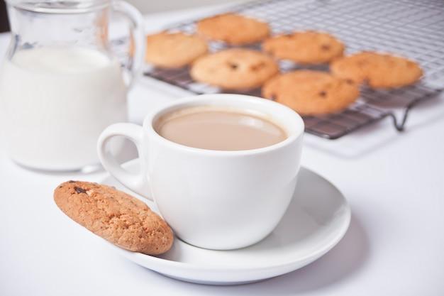 Tasse tee mit milch, selbst gemachte plätzchen auf dem weiß