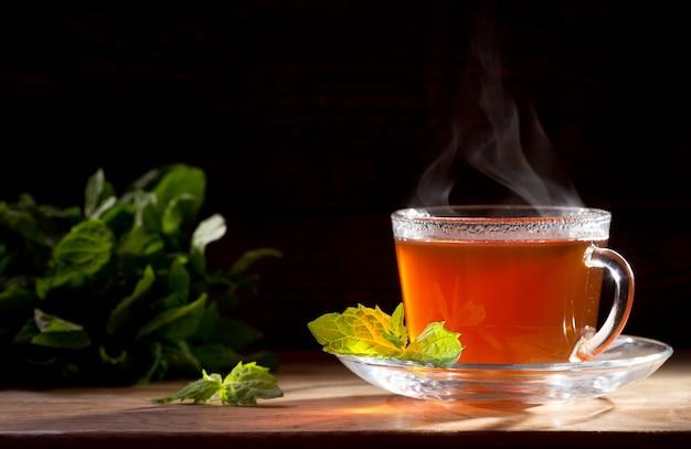 Tasse tee mit minze auf einem holztisch