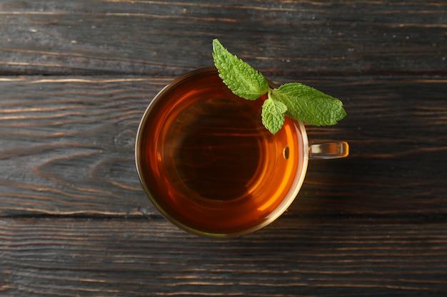 Tasse tee mit minze auf holz, draufsicht