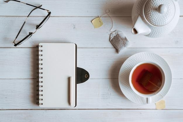 Tasse tee mit notizbuch auf weißem holztisch, draufsicht