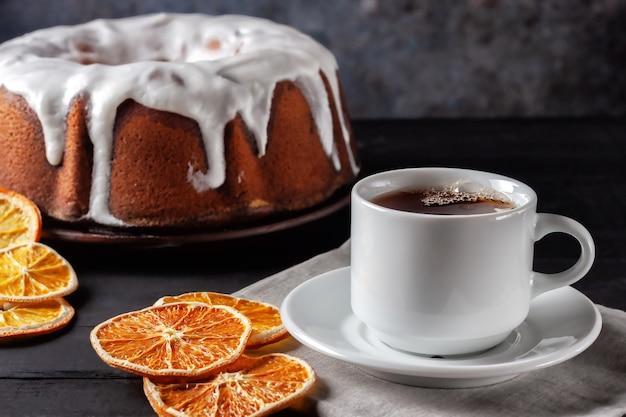 Tasse tee mit orangen und einem stück hausgemachtem muffin