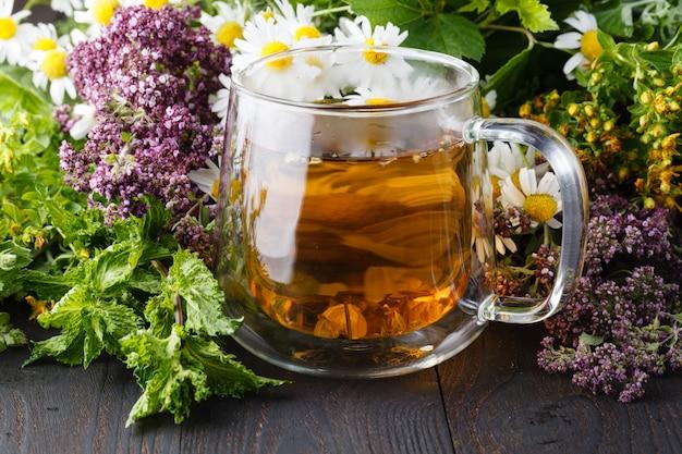 Tasse tee mit oreganokraut auf holztisch