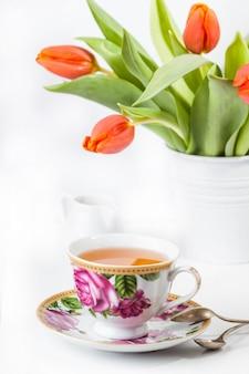 Tasse tee mit roten tulpen über weiß