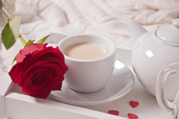 Tasse tee mit roter rose auf weißem tablett