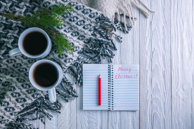 Tasse tee mit schal und notizbuch