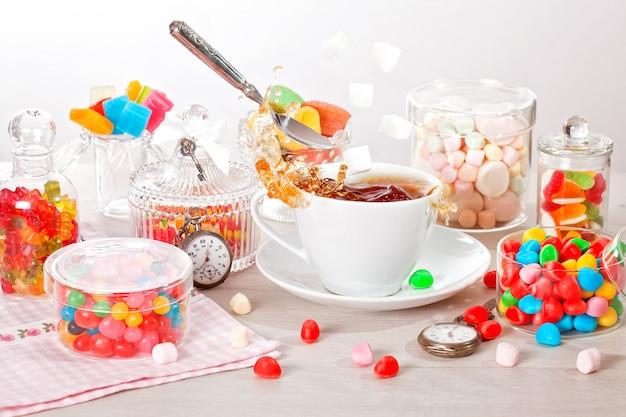 Tasse tee mit sortierten bunten süßigkeiten, fliegendem löffel, zucker und spritzern für den geburtstag des kindes
