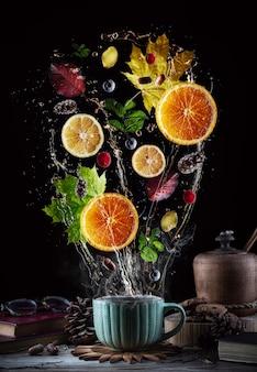 Tasse tee mit spritzern und früchten.