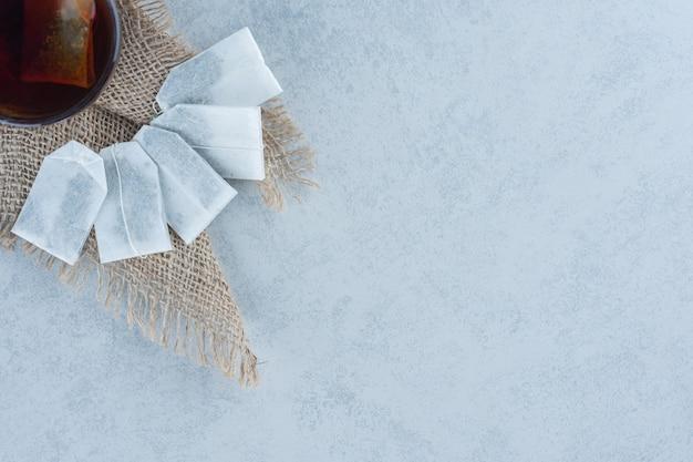 Tasse tee mit teebeuteln auf handtuch auf marmor.