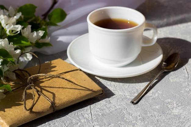 Tasse tee mit unter frischer frühlingsblume. frühstück an einem sonnigen tag im freien. hübsche geschenkbox mit einfachem braunem bastelpapier umwickelt und mit jute verziert. konzept der vorbereitung auf die feiertage