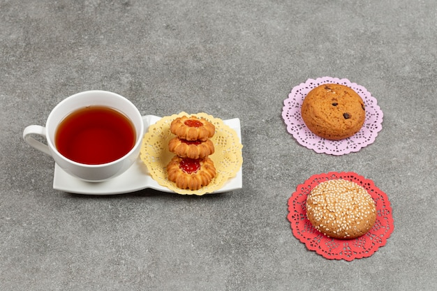 Tasse tee mit verschiedenen keksen auf marmoroberfläche