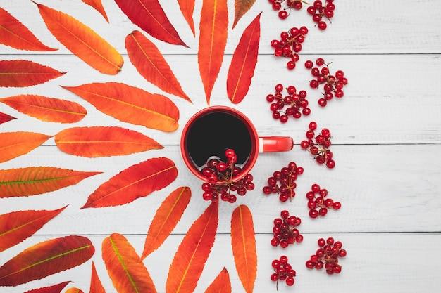 Tasse tee mit viburnum-beeren und rotem herbstlaub auf holzbrettern.