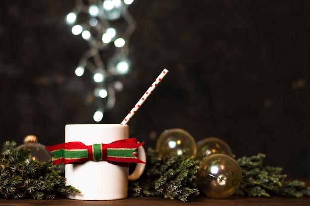 Tasse tee mit weihnachtslichtern im hintergrund