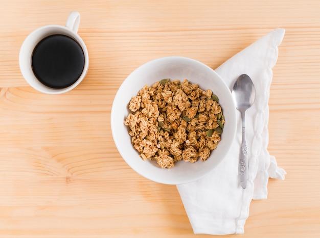 Tasse tee mit weißer schüssel granola- und kürbiskernen auf hölzernem schreibtisch