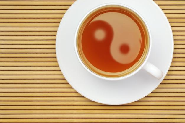 Tasse tee mit yin yang symbol auf einer rattanmatte