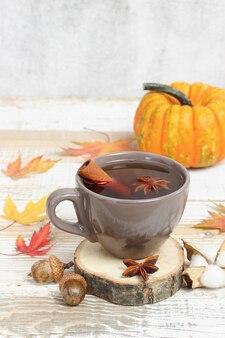 Tasse tee mit zimt und anis auf holzständer mit blättern und kürbis im hintergrund