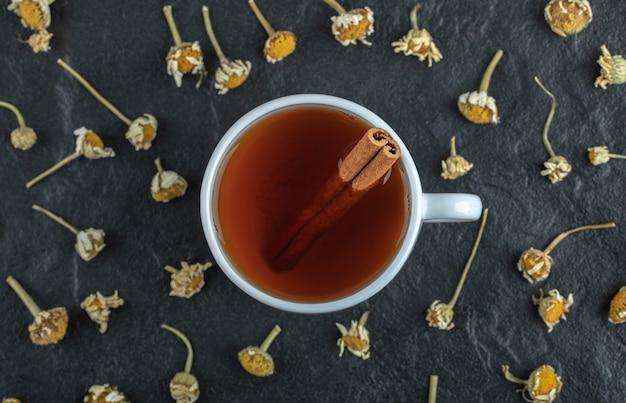 Tasse tee mit zimt und haufen getrockneter kamille.