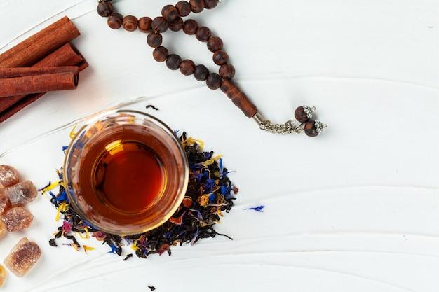 Tasse tee mit zimtstangen auf dem tisch