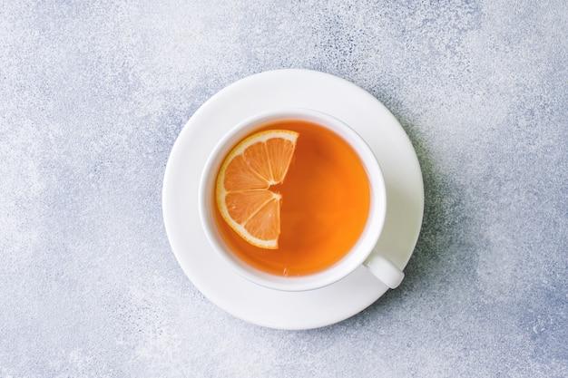 Tasse tee mit zitrone auf dem tisch. ansicht von oben.